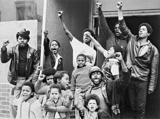 "Black youth giving the Black Power salute outside a ""liberation school"" run by the Black Panther Party in SF in 1969."