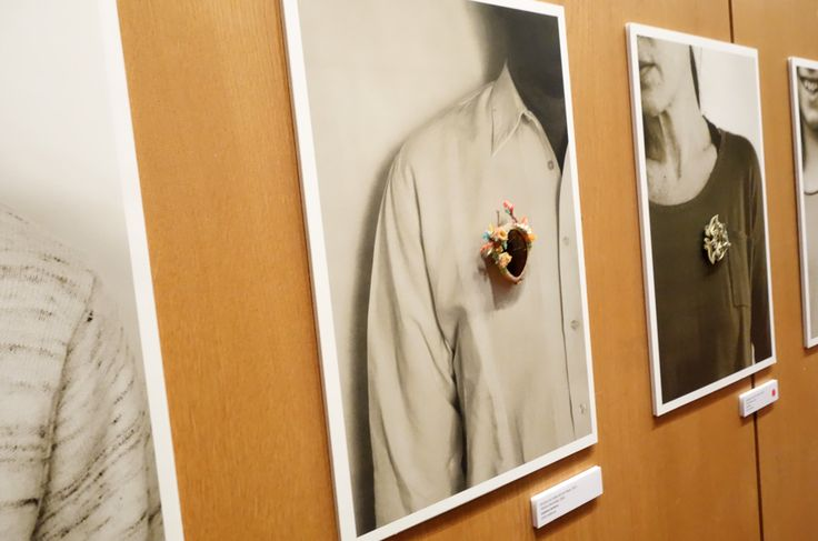 Schmuck 2013 – Brooches displayed on enlarged photos of men & women.