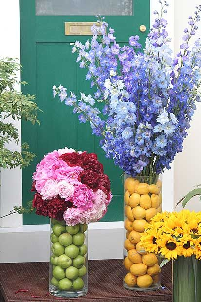 Fruit in vases with contrasting color flowers.