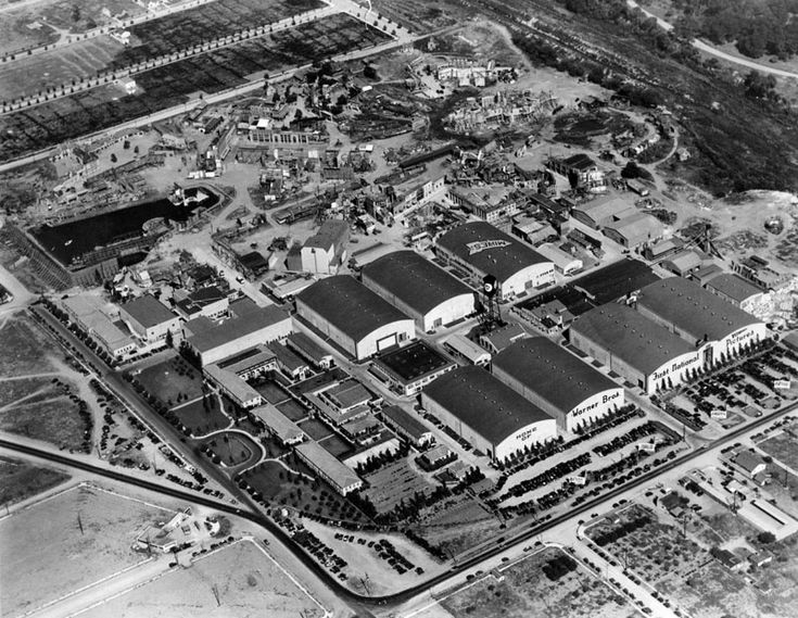 An aerial view of the studios of the Warner Bros.-First National studios in Burbank (1929). Warners bought First National in 1928, and the Warner Bros. sign is visible on one of the north stages facing Barham Boulevard toward the bottom of the picture. Stage 7 had not yet been built. The backlot is seen occupying about half of the real estate.