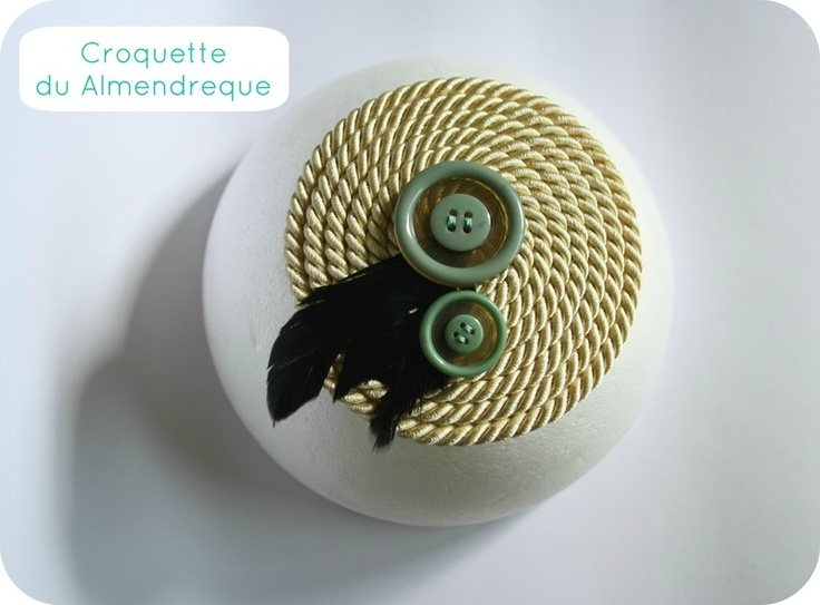Tocado beige con dos botones vintage y adorno de plumas negras con reflejos verdes. Producto único y exclusivo. Disponible en la tienda Croquette du Almendreque Dawanda España.