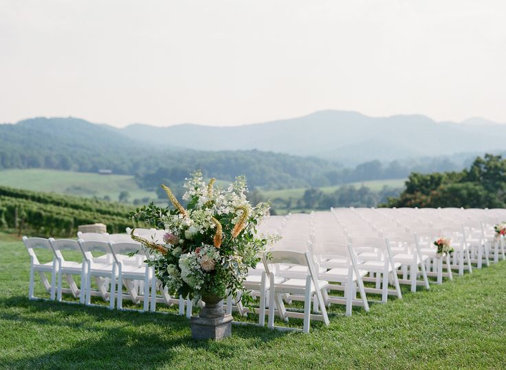 White Ceremony Chairs At Pippin Hill Farm With Large Floral Arrangement  Entrance.