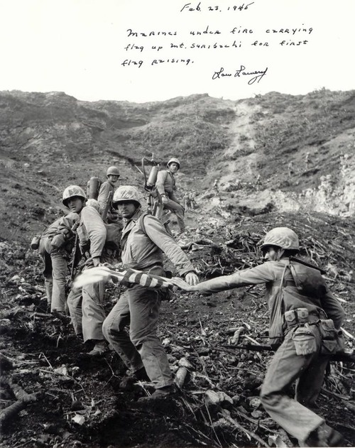 "Marines carrying the first flag up Iwo Jima.--The famous flag is the SECOND flag brought up there because the ""first one wasn't big enough."""