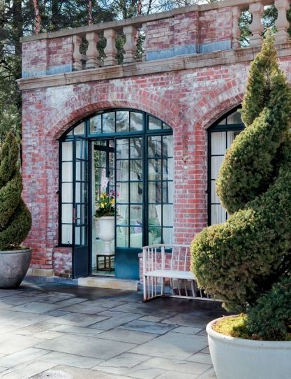 Brick and black casement arched windows/french doors (and swirly topiaries)