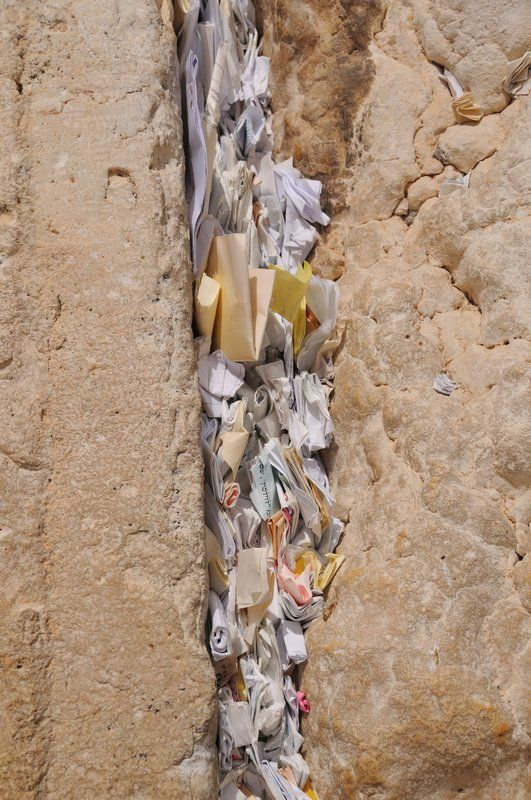 The Wailing Wall in Jerusalem, Israel  prayers written down on paper then jammed into cracks in the Wall.