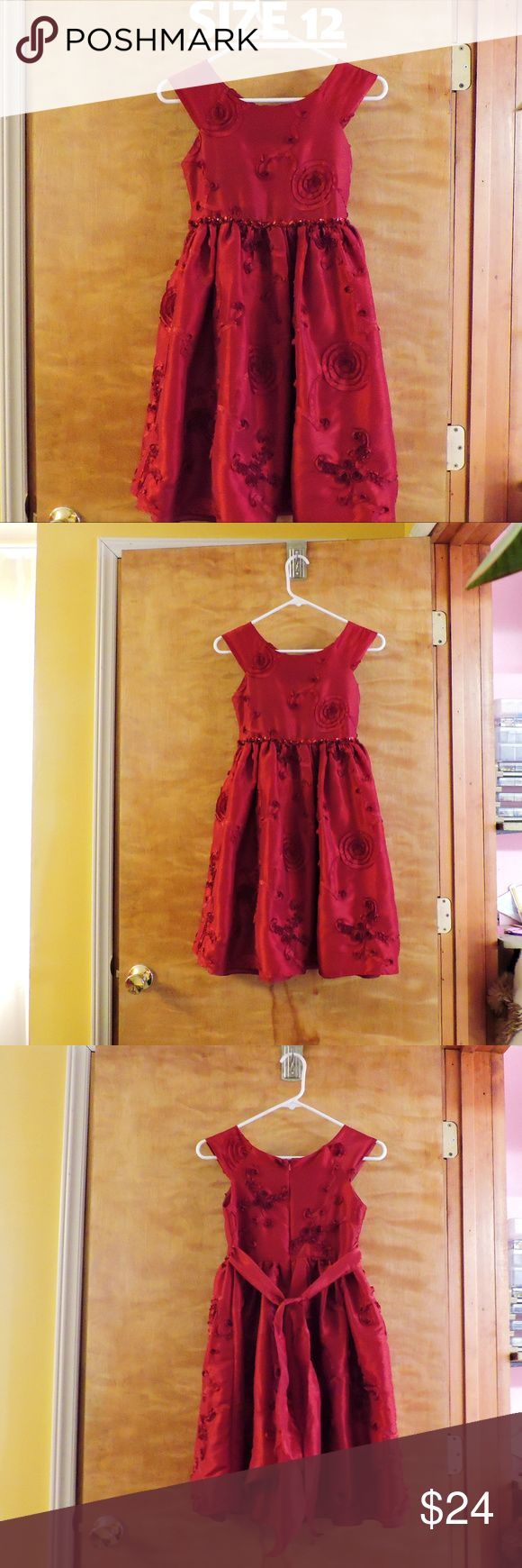 embellished girls dress, size 12, dark red size 12 in girls.  this dress is a deep dark red.  I had difficulty getting the true color for you but the pictures of the dress hanging is the closest to true color.  embellishments are shown.  also has a hidden zipper in back.  this dress has minor flaws that may or may not need fixed .. you decide ...  the last 2 pictures show the flaws.  (1) back belt holder (by zipper) (2) the waist front embellishment is loose on one edge.   definitely a below…