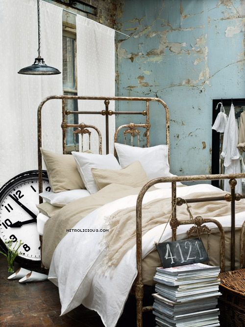 Industrial vintage charm - love the clock peeking around the end of the bed.