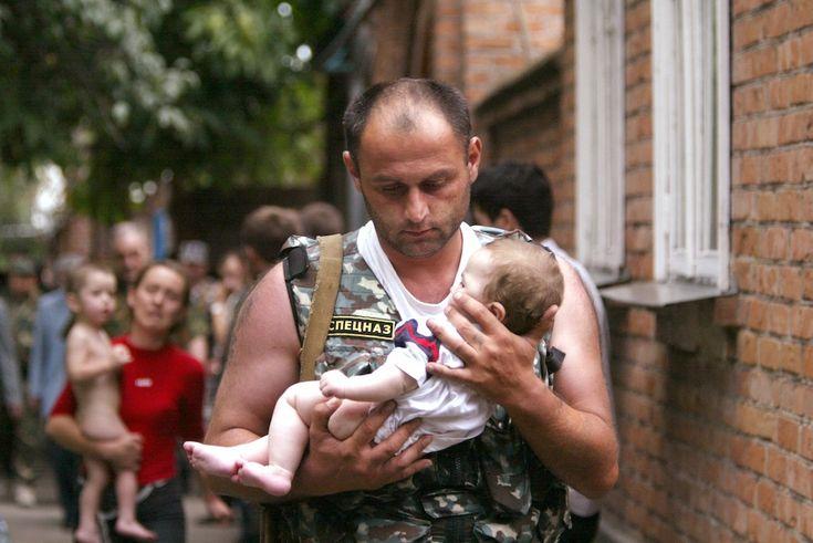 Un poliziotto russo porta un bambino piccolo fuori dalla scuola di Beslan, Ossezia del Nord, attaccata da un gruppo di separatisti ceceni l'1 settembre 2004. I separatisti tennero in ostaggio 1.200 persone per più di due giorni, in gran parte bambini. Durante l'assedio e nel disordinato assalto delle forze speciali russe morirono 385 persone mentre quasi ottocento furono ferite. Fu il più grave attacco terroristico mai avvenuto in Russia. (REUTERS/Viktor Korotayev/Files)