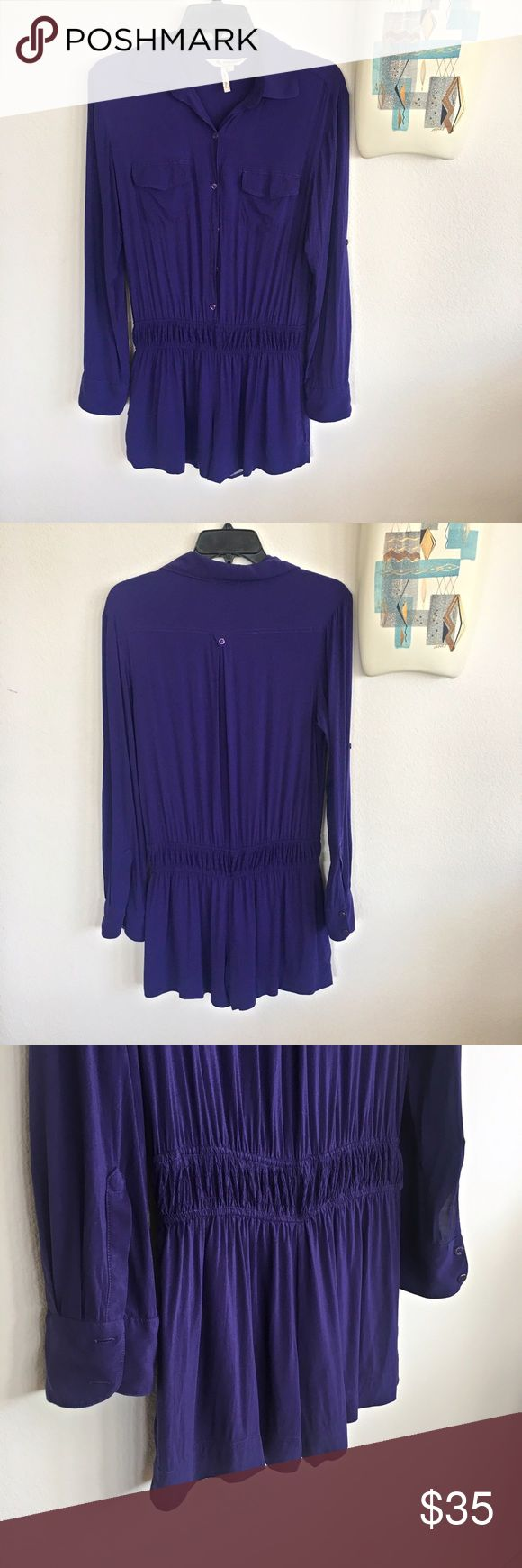 BCBGeneration Romper Bluish purple long sleeve romper from BCBG with the option to button up sleeves. Romper is lined from the waist down. Banded waist. Two breast pockets. Button down to the waist. This is so cute! The color is midnight blue but it has a purple tint to it. There are a few blemishes which are very hard to see. Please see pictures 6 and 7.  Two Fabric blemish on the back of romper, but it is difficult to see when on. In all around good condition. BCBGeneration Pants Jumpsuits…