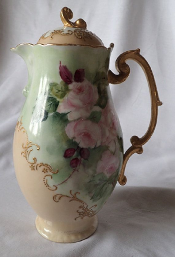 This is a beautiful hand painted Jean Pouyat Limoges water jug or pitcher decorated with pink roses against a background of green and plum coloured foliage with gilded scrolls and flowers on a blush coloured body. The blush and white lid is also decorated with gilded scroll details and a gilt handle. It dates from 1891 -1932. It measures 23cm in height (9.05 inches). It is in good vintage condition, there is some wear to the gilding on the rim(see photo 3) and more minor wear to the…