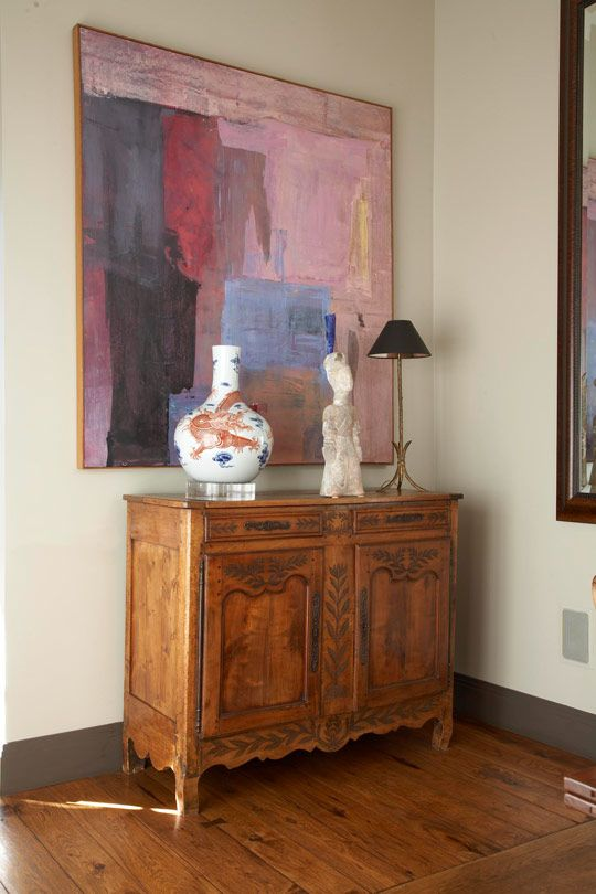A Large Colorful Painting Presides Over French Chest In The Dining Room