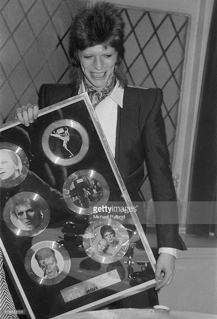 English singer-songwriter David Bowie (1947 - 2016) with an award 'For Outstanding Musical Achievements', from RCA Records, January 1974. The award features Bowie's first six albums for the company.