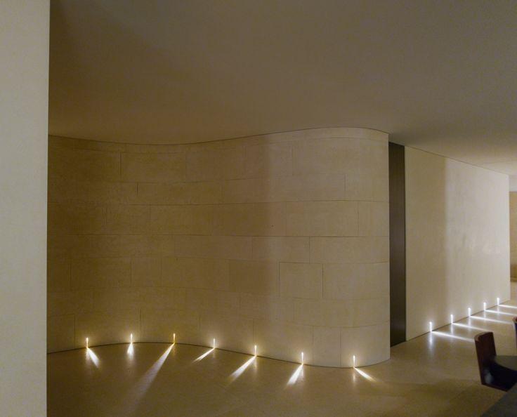 Ancora la parete curva che di sera è attraversata dai tagli di luce dei segnapasso Raggio di Claudio Silvestrin per Viabizzuno