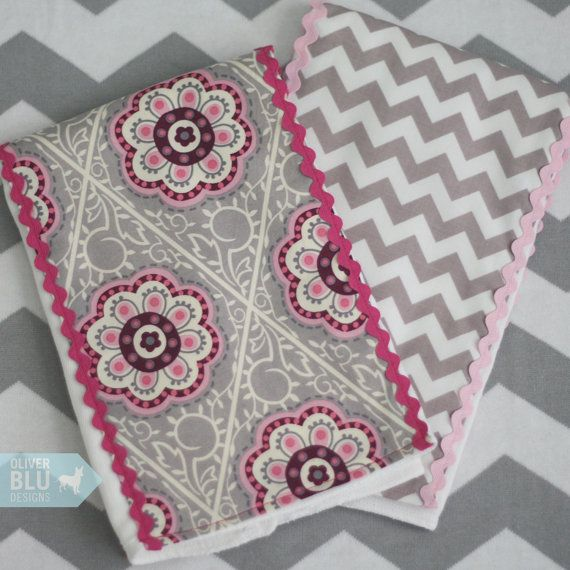This set of two boutique burp cloths makes the perfect gift for baby girl. Made from generously sized premium quality cloth diapers, each cloth measures 14 x 21 inches. Trimmed in designer fabrics with coordinating rick rack trim. Perfect for stocking the diaper bag and quick, stylish wipes at home or on the go. Large enough to cover your entire shoulder for burping or for using a changing pad on the go.    This set ships within 5 days and may be sent directly to a gift recipient with…