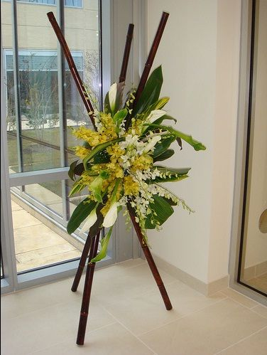 Suspended in the center of a tripod made of 6 foot Bamboo Poles, the soothing combination of yellow Cymbidium, white Dendrobiums, white and green Calla Lilies and varied tropical leaves is a lovely variation on the usual Sympathy presentation.