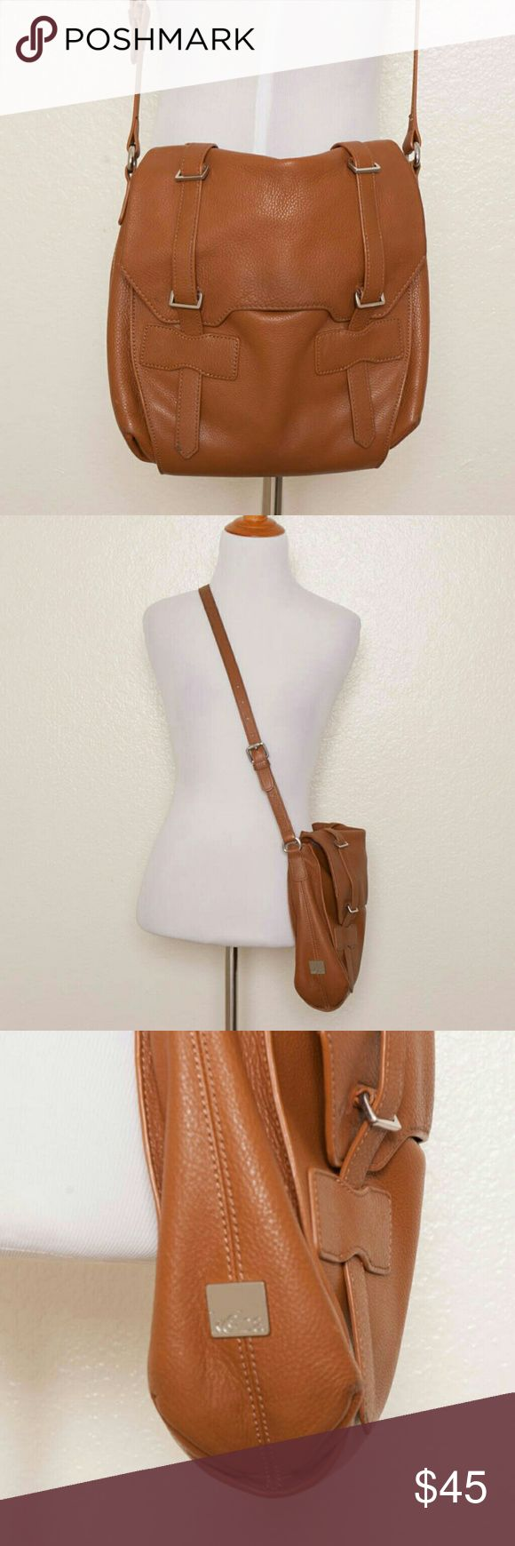 Kooba Jane Leather Crossbody ?Jane? Crossbody in ?Luggage? brown colorway Leather With Polished Silvertone Hardware Side Logo Plate 42'' Crossbody Strap With 18'' Drop; 8'' Top Handle With 3'' Drop Measures Approximately 10'' At Widest X 9?'' Tall At Center X 5'' Deep; Weighs 2 Lbs  Condition: Bag is clean and shows moderate wear. Some light scratches on the silvertone hardware; light wear at two of the bottom corners; darkened area on the back; heavy wear on the strap with some fraying and…