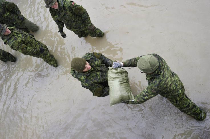 Corporal Ricardo Moreira from 2nd Battalion, Royal 22 Regiment, from Valcartier, Quebec passes sandbags from the vehicle to the flooded homes.  Photo credit: Sgt Norm McLean, Canadian Forces Combat Camera  © 2011 DND-MDN Canada   #StrongProudReady