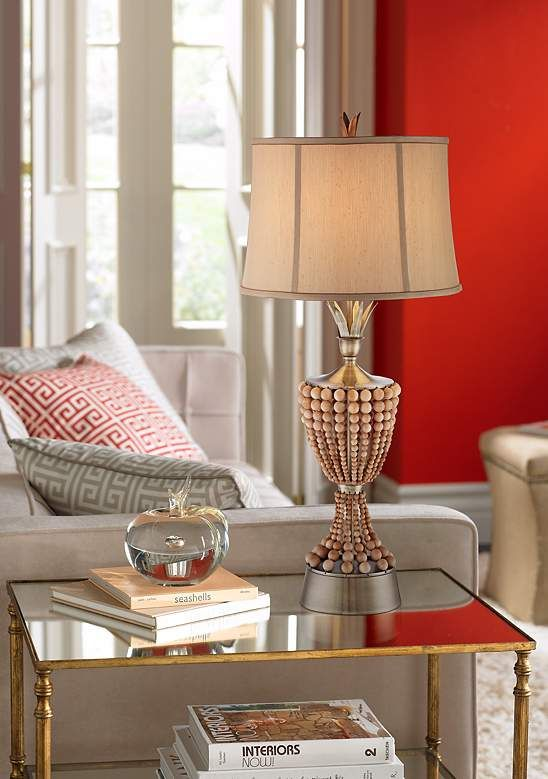 A tropical inspired table lamp in brass and wood finishes, with a unique beading detail in the base.