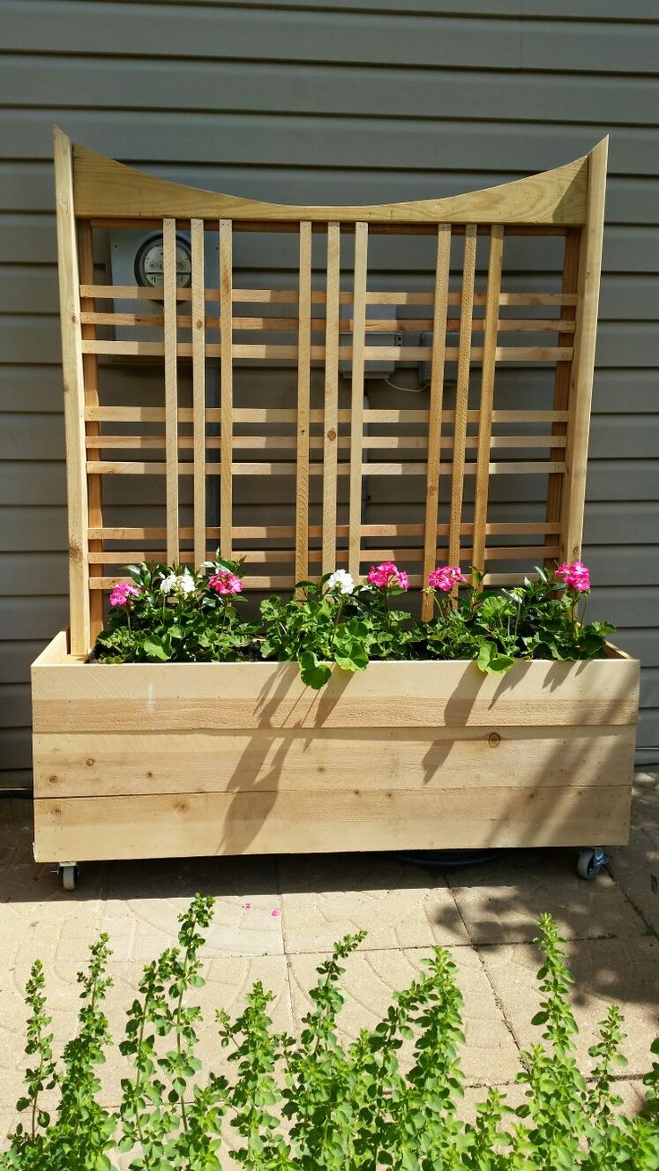 Planter with trellis I made to cover up electrical box and meter, cable box, and telephone box. Now the flowering vines just have to grow. Made from cedar fence boards over a frame of 2x4s . Open in the back for storage of watering equipment. I used 3 over the rail deckboxes (Home Depot) and they are just resting on the frame. Wheels help me move the planter out of the way when needed.