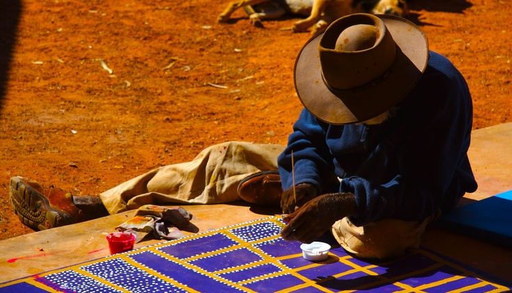 An artist painting his story in the Yuendumu area of the Northern Territory, Australia