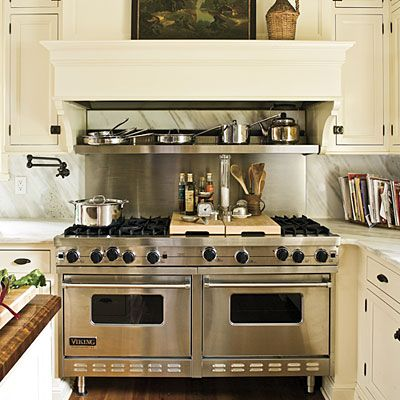 Close-up of this awesome cooktop, stainless steel backsplash, stainless steel shelf, and mantle-like vent hood. I love the slim little cabinets on either side of the cooktop for cooking oils, spices, etc.