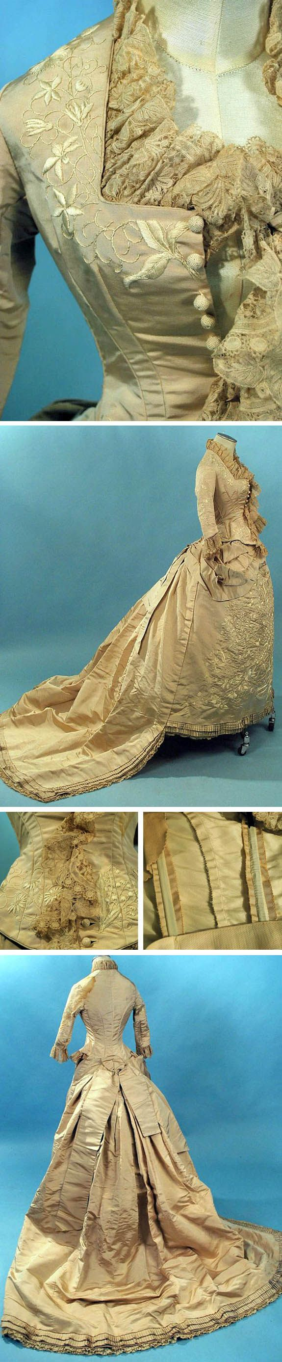 Silk faille wedding gown, circa 1870s. Embroidered front panel on skirt repeated on bodice in flowers and vines. Square neckline on stayed bodice with hand Brussels lace trim and crochet ball buttons. One-piece dress with waistband closing in back. Draped and gathered detailing with swags and box pleats in back and train. Lined in netting with dust ruffle interior hem. via Extant Gowns.