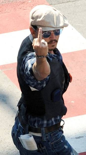 Johnny Depp gestures to paparazzi at the Nice, France airport when he arrived with his family and paparazzi were yelling his children's names to try to get photos of them.
