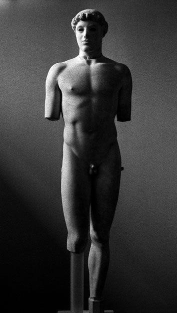 Kritios, Efebo, 480 a.C. Marmo, h. 86 cm. Atene, Museo dell'Acropoli. Il kouros gravita sulla gamba sinistra arretrata, con la conseguente rotazione del bacino che, dallo stesso lato, si solleva. Tale soluzione contrasta fortemente con l'appoggio su ambedue le gambe proprio dei kouroi arcaici, pur lasciando inalterata la frontalità del busto. E' in questo periodo, del resto, che si pone il problema più tipico della statuaria greca: quello dell'equilibrio e della gravitazione.