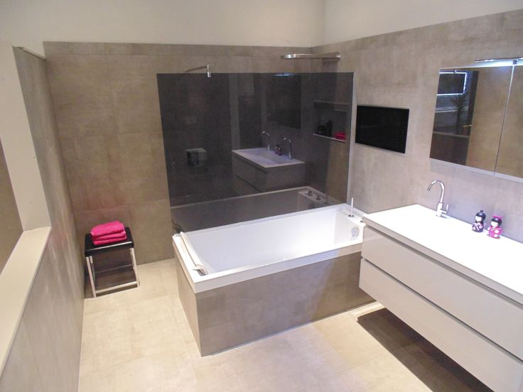 Betonlook tegels in grootformaat op de vloer en tegen de wand met een accent op de zijkant van het bad met stroken