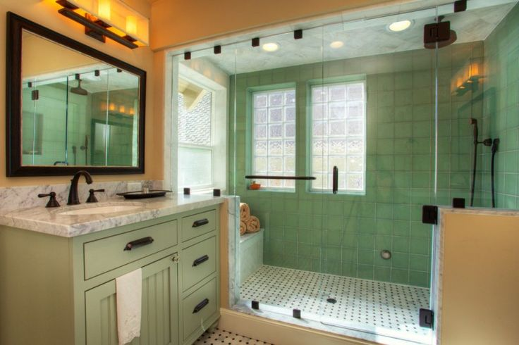 craftsman bathroom with shower are in green tiles floor, green tiles wall, green marble ceiling, sink area with brown walls, green cabinet with grey marble top, mirror