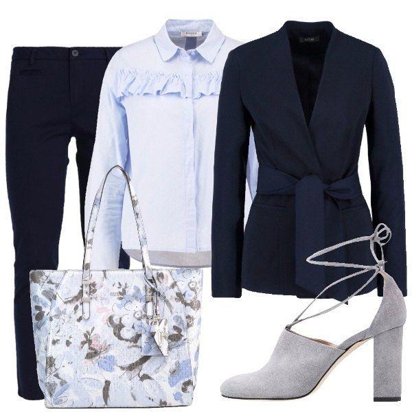 Questo outfit è composto da pantalone blu, camicia classica celeste resa particolare da piccole ruches, blazer con cintura in vita, scarpe grigie con tacco grosso e lacci e shopper con fantasia floreale.