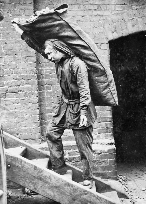 INDUSTRY DURING FIRST WORLD WAR (Q 54625)   A female worker carries a sack of coke on her back up a flight of stairs at a London gas works during the First World War.