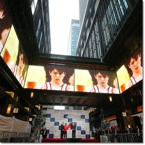 ▼日本選手の活躍を大型モニターで楽しむ 東京  2020年東京オリンピック・パラリンピックへの気運を盛り上げようと、東京の中心部で、リオデジャネイロ大会の日本選手の活躍を映像で楽しめるイベントが始まりました。  このイベントは、リオデジャネイロ大会の閉幕に合わせ、東京大会の組織委員会とスポンサーの不動産会社が企画し、東京・中央区日本橋のビルを挟んだ通りの5メートルほどの高さに、長さ9メートルの大型モニターが設置されました。  20日午後に行われた点灯セレモニーには、先月のオリンピックのレスリングで銀メダルを獲得した吉田沙保里選手や、組織委員会の森喜朗会長などが出席しました。  出席者がスイッチを押すと、吉田選手や体操の内村航平選手など、リオデジャネイロ大会の日本選手の活躍の様子がモニターに映し出されました。  また、周囲のビルの壁には、選手たちの大型写真や東京大会のエンブレムが描かれた垂れ幕なども飾られ、雰囲気を盛り上げていました。