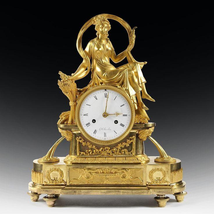 Pendule en bronze doré et ciselé représentant Cérès en déesse de la Fertilité, de l'Agriculture, symbolisant l'ÉtéÉlégamment drapée, la faucille à la main, elle est assise sur une fontaine. La base est décorée de roseaux et d'épis. De la base surgissent deux fontaines latéralesCadran signé Gel. Le Roi à ParisEn parfait état de conservation et de fonctionnementÉpoque fin XVIIIe - début XIXe