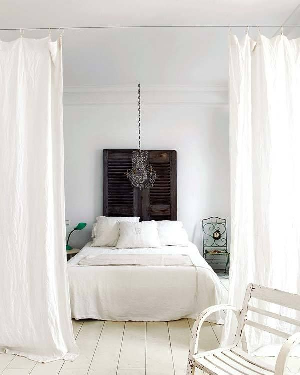 crisp white bedroom with black shutters against the wall.