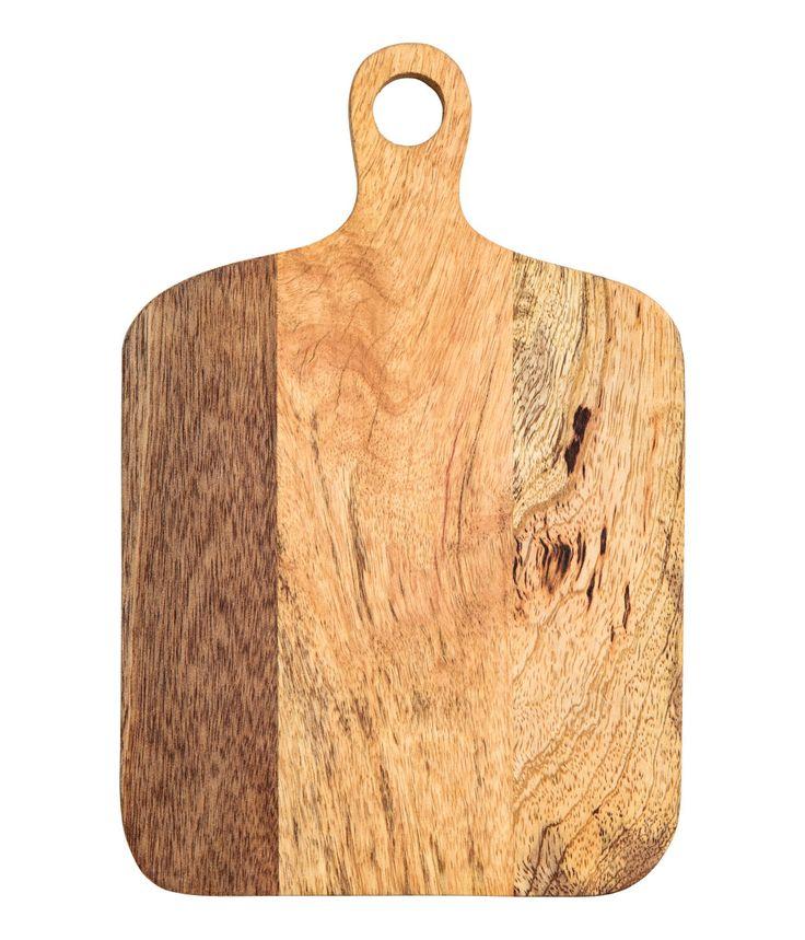 Beige. En liten skärbräda i trä. Skärbrädan har hangtag med hål för enkel upphängning. Bredd 18,5 cm, längd 27,5 cm (inklusive handtag).