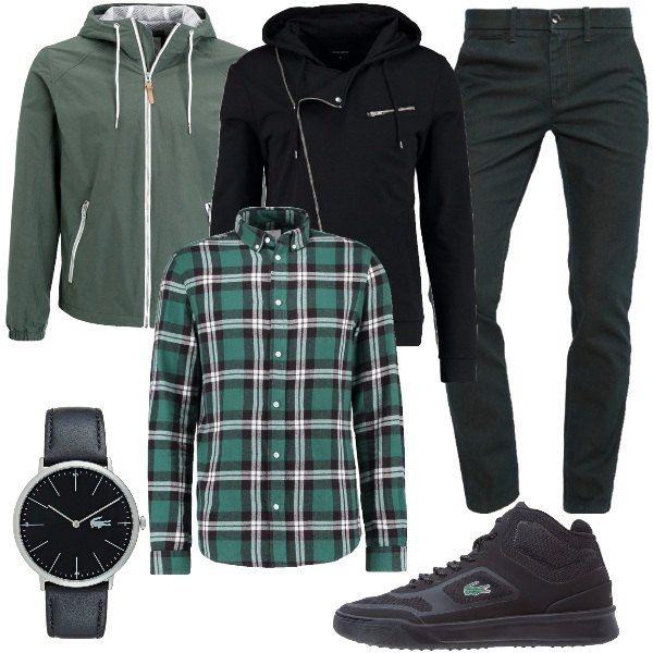 Total look maschile formato un jeans slim fit verde scuro, una camicia a scacchi verde, bianco e nero, una felpa nera con zip laterale e cappuccio e una giacca leggera. L'outfit è completato da un paio di sneakers alte e un orologio in nero.