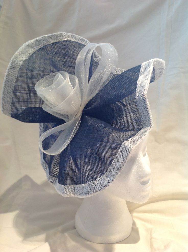 The Elizabeth is an extra large fascinator on a black head band with sapphire blue gathered sinamay with a buttermilk trim the large centre piece is a buttermilk crinoline bow surrounding a pearl detailed rose. $150 AUD.