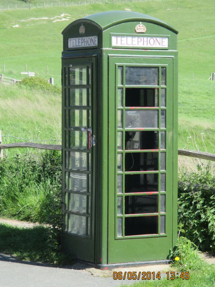 K6 GPO phone box in green paint photographed at the Seven Sisters Country Park on the A259 near Seaford, East Sussex in May 2014.