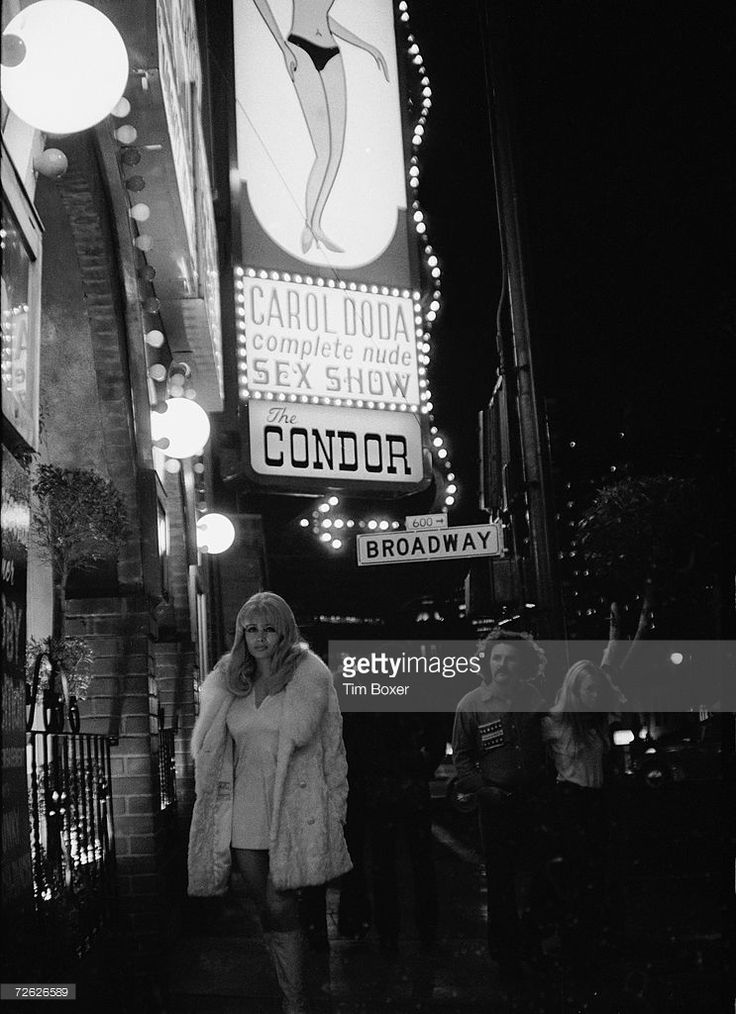 American striptease artist Carol Doda poses in a coat, miniskirt, and boots under a marquee baring her name outside the Condor, a strip bar in San Francisco, California, 1970s.