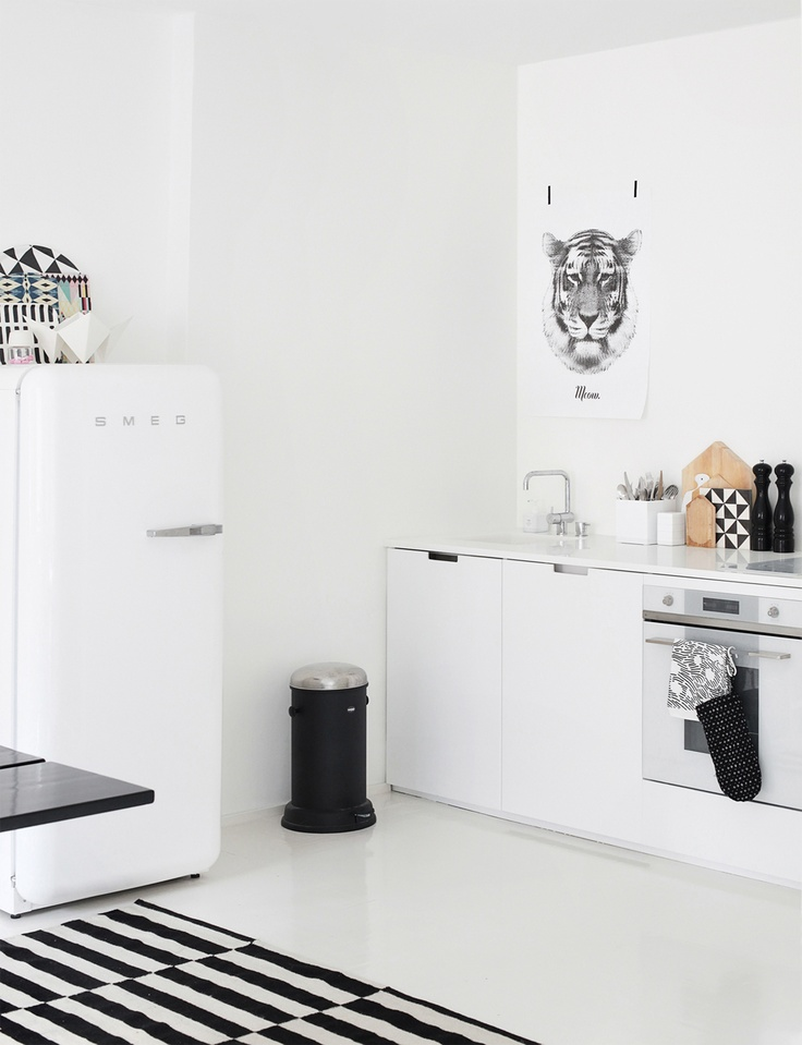 Black & white kitchen , with cool artwork & neat accessories (plus who doesnt love a smeg fridge?)