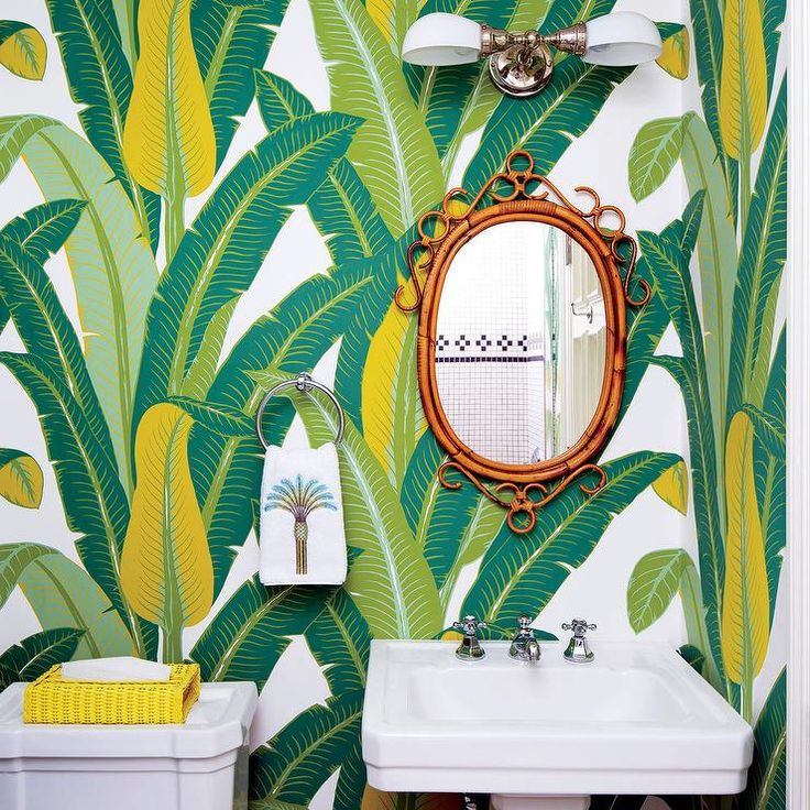 Schumacher Tropical Isle Wallpaper covers the wall of this gorgeous yellow and green powder room boasting an oval rattan mirror mounted beside a polished nickel towel ring over a pedestal sink lit by a 2-light nickel sconce.