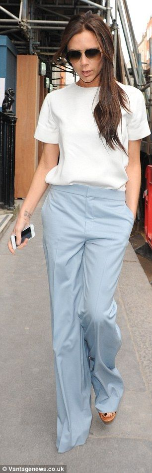 Bold in brights: In baggy blue trousers the former Spice Girl shows just the merest glimps...