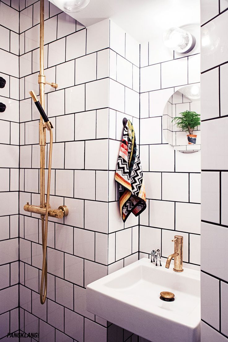 Bathroom white tiles black grout, brass