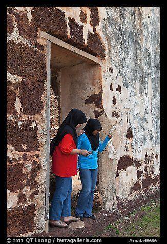Malay girls exit on St Paul church doorway. Malacca City, Malaysia
