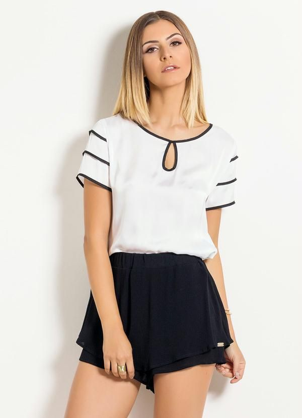 White blouse with black trim, double shorts.