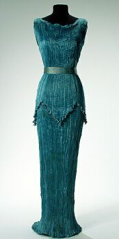 Fortuny Peplos Gown   Late 1920s/early 1930s   Of aquamarine pleated silk, sleeveless, with ruffled drawstring neckline, overtunic with pointed hem sewn with brick tone Venetian glass beads, the beads repeated at shoulders, gold stenciled belt