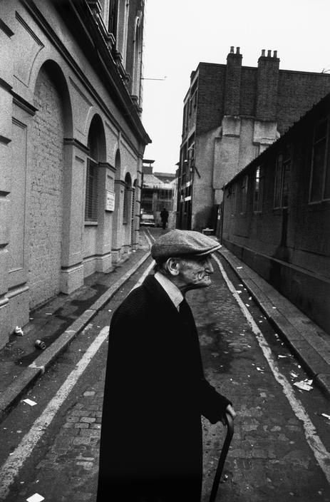 G.B. ENGLAND. London. Spitalfields. Old man walking stick in rubbish lined back streets of East London. 1976.