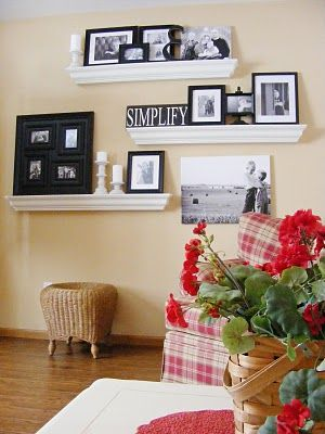 Wall gallery with crown molding ledges for living room - love the pop of color with the red plaid chair and happy geraniums
