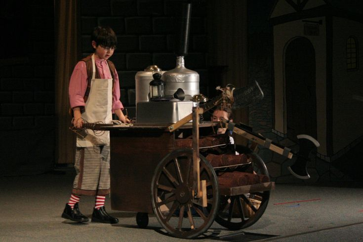 """BEAUTY & BEAST JR.:Maurice, Belle's father and his crazy contraption. Maurice was a simple pair of short pants, his own socks. The contraption began with a cart found at the thrift store and then """"cherried out"""" by my husband, using a C02 fire extinguisher in the chimney. The silver container is just an old 5-gallon water bottle spray painted silver. The CO2 extinguisher puffed through the neck of the silver 5-Gal container. The handle to operate the CO2 was attached to cart handle."""